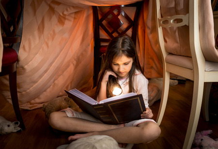 night view: Portrait of cute girl sitting under blanket and reading a book
