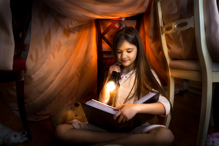 Little cute girl reading book in self-made house with flashlight