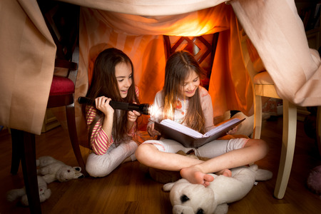 Two cute girls sitting under blankets and reading book with flashlight Archivio Fotografico