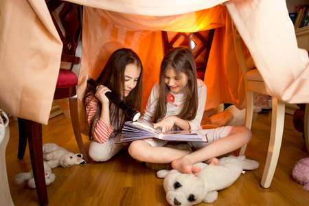 Beautiful cute girls reading book with flashlight at house made of blankets