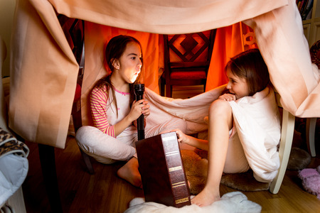 flashlights: Two sisters telling scary stories under blanket at night