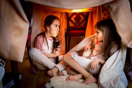 Portrét starší sestře vyprávět strašidelný příběh mladší v pozdní noci v ložnici