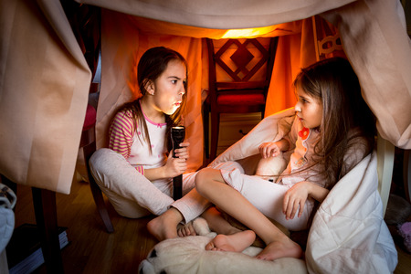 creepy monster: Portrait of elder sister telling scary story to younger one at late night in bedroom Stock Photo