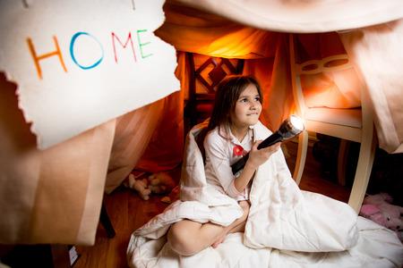 Happy smiling girl lighting bedroom at night with flashlight