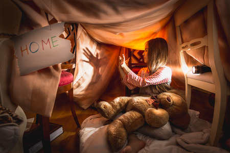 Cute girl made theater of shadows in self-made house at bedroom