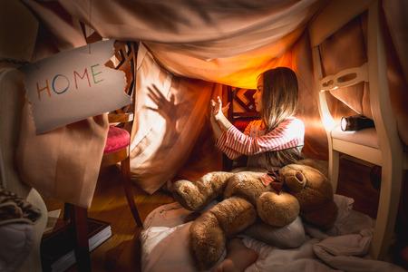 Roztomilá dívka dělal divadlo stínů v self-vyrobené domu v ložnici Reklamní fotografie