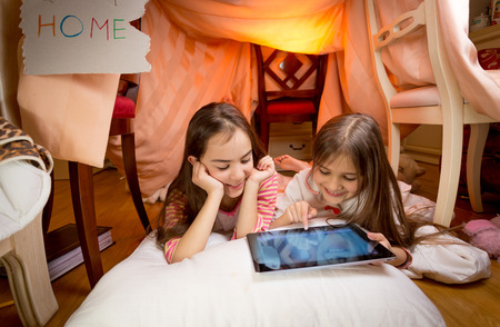 Two cute girls lying on floor at bedroom and playing on digital tablet Foto de archivo