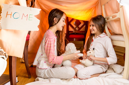 Two smiling girls playing in house made of blankets at bedroom Foto de archivo