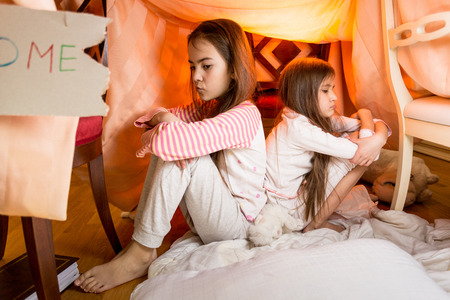 resentful: Two little resentful sisters sitting on floor at bedroom back to back Stock Photo