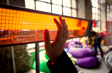 Closeup shot of woman warming hands at infrared heater