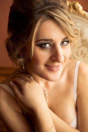 ojos verdes: Retrato de mujer linda rubia de ojos verdes posando en la habitación de lujo