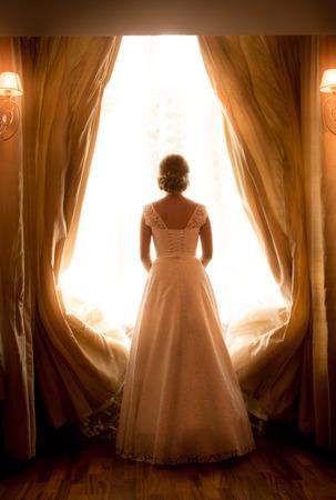 sexy bride: Silhouette shot of elegant bride looking at window in hotel room