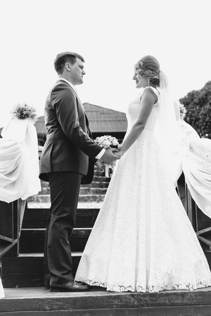 Black and white shot of happy bride and groom holding hands and looking at each other