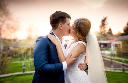 newly married couple: Portrait of elegant newly married couple kissing in park at sunset