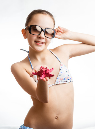 Portrait of cute girl in sunglasses showing red starfish on hand