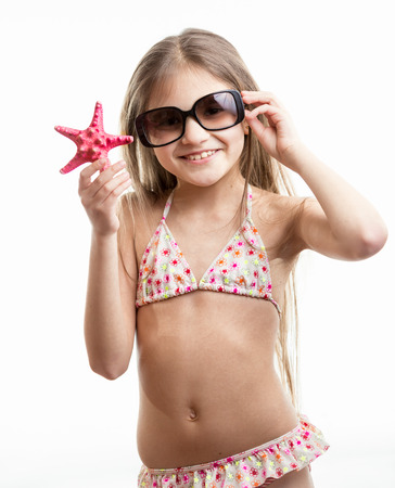 isolated portrait of happy smiling girl in sunglasses posing with red starfish photo