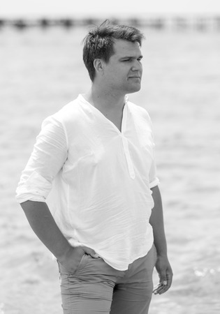Black and white portrait of handsome young man posing on beach Stock Photo
