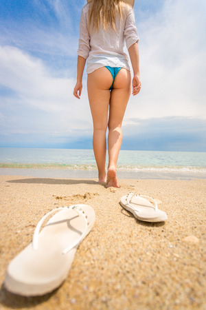 flip flops: Closeup shot of young woman taking off flip flops and and walking on the beach Stock Photo