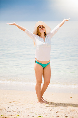 lifting hands: Beautiful woman in white shirt and hat standing on beach and lifting hands up Stock Photo
