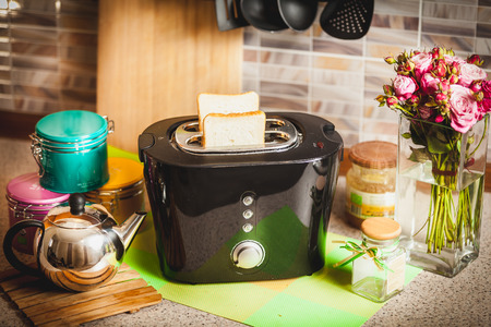 Black toaster with bread slices on kitchen table photo