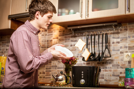 popped: Young handsome man catching fresh popped out toasts on white plate Stock Photo