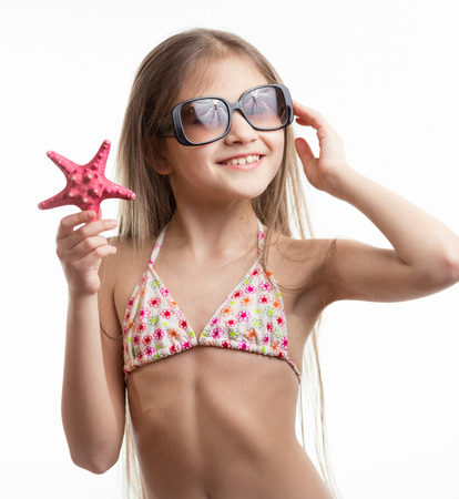 Isolated portrait of cute smiling girl in sunglasses posing with starfish