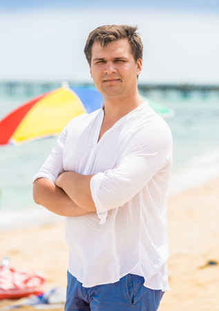 mani incrociate: Portrait of handsome man with hands crossed posing at beach