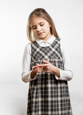 Portrait against white background of little schoolgirl counting on fingers photo