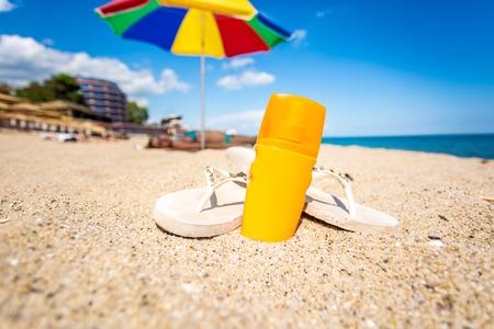 Close-up foto van gele zonnebrandolie en flip flops liggend op zandstrand