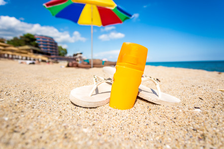 Closeup photo of yellow suntan lotion and flip flops lying on sandy beach