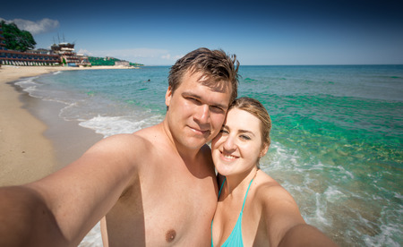 making love: Happy couple in love making selfie on seashore at sunny day Stock Photo