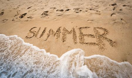 Word Summer written on wet sand at seashore photo