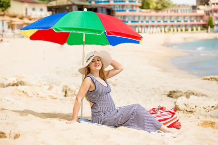 awaiting: Beautiful woman awaiting for baby relaxing on the beach at hot sunny day