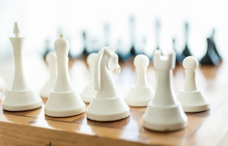 leisure game: Closeup photo of white chess piece set on wooden board Stock Photo