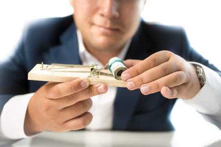 Isolated closeup photo of man in suit taking money out of mousetrap