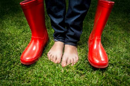 rain boots: Foto del primer de mujeres pies de pie sobre la hierba verde al lado de las botas de lluvia de color rojo