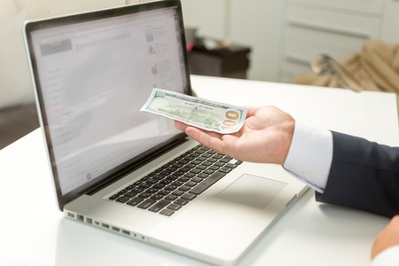 Closeup photo of businessman holding banknote on hand and giving it to computer Stock Photo