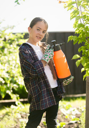 exterminating: Smiling girl exterminating insects in garden with toxic spray