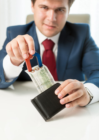 pulling money: Portrait of greedy businessman pulling money out wallet with use of magnet Stock Photo