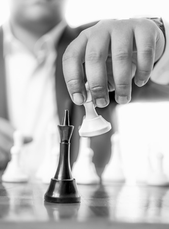 pawn king: Black and white closeup photo of businessman beating chess king with pawn