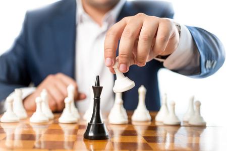 ajedrez: Foto de detalle de hombre de negocios jugando al ajedrez y golpeando rey negro Foto de archivo
