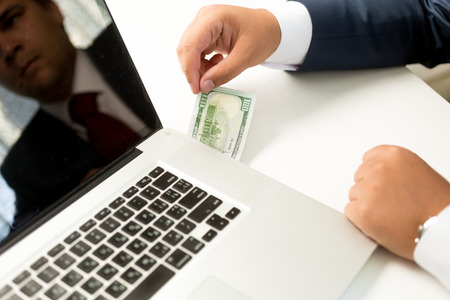 pulling money: Conceptual photo of businessman receiving digital money transfer. Man pulling dollar bill out of laptop Stock Photo