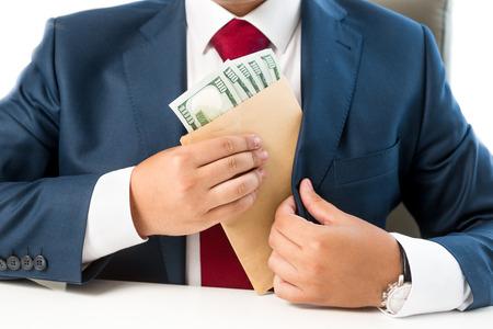 Closeup conceptual photo of bribed man putting money in the suit pocket Foto de archivo