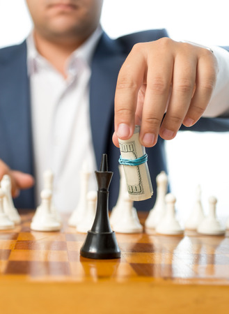 Closeup photo of businessman playing with twisted dollars at chess game photo