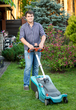 mowing grass: Handsome young man mowing grass at house backyard Stock Photo