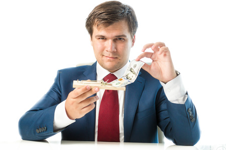 Portrait of cunning businessman taking dollar bill out of mousetrap Stock Photo