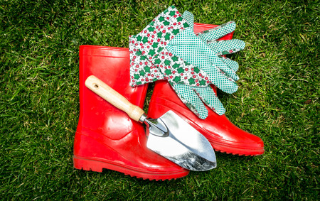 gumboots: Closeup photo of garden tools and red gumboots lying on fresh green grass Stock Photo
