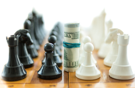 winning stock: Conceptual shot of twisted dollar bills between white and black chess pieces Stock Photo