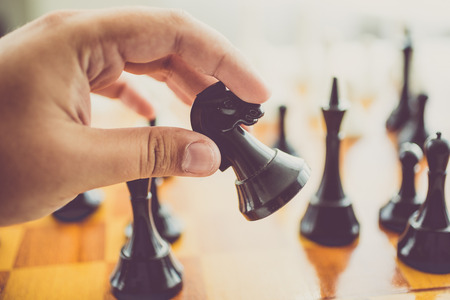 chess piece: Closeup toned photo of man making move with black horse at chess game Stock Photo