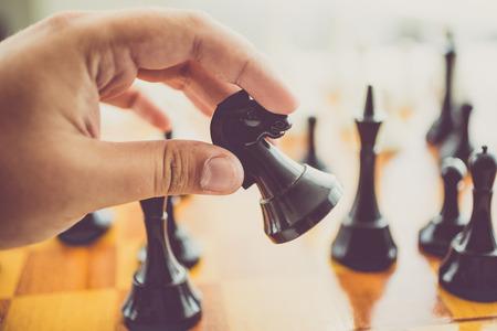 ajedrez: Foto tonos Primer del hombre que hace movimiento con el caballo negro en el juego de ajedrez